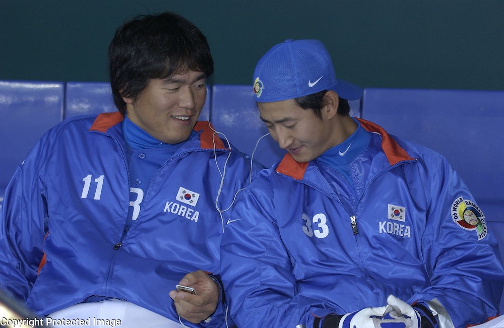 Team Korea's Hee Seop Choi (L) and Yong Taik Park (R)  listen to music before the start of the Pool A Championship game against Team Japan of the World Baseball Classic at Tokyo Dome, Tokyo, Japan.