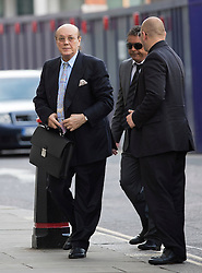 © London News Pictures. 14/08/2012. London, UK. Cypriot businessman Asil Nadir (left) arriving at Central Criminal Court, Old Bailey, in London escorted by his security on August 14, 2012 where the jury is currently considering a verdict  in the Polly Peck fraud case. Nadir, who fled to Cyprus in 1993 after the charges were first brought, is accused of £34m fraud at his firm Polly Peck. Photo credit : Ben Cawthra/LNP