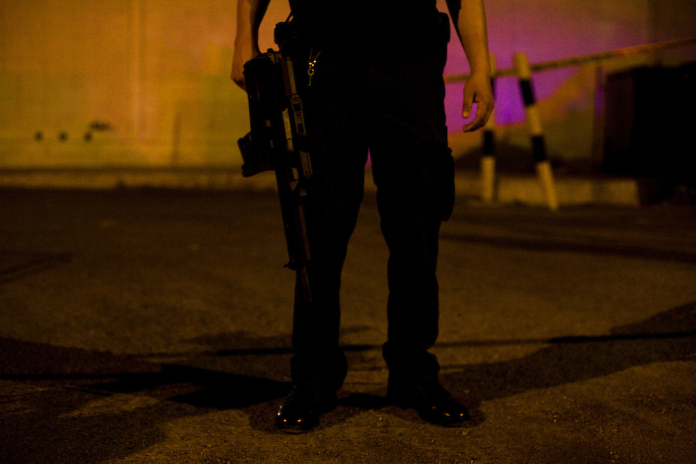 A CIPOL state police office stands guard of a murder scene behind a casino in Ciudad Juarez, Chihuahua on May 15, 2010.