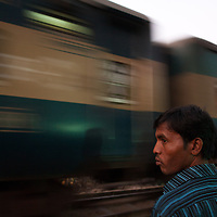 A man stands next to the railway track as the train passes at dusk in Srimongol in the tea growing region of north east Bangladesh. Many people walk and live on and around railway tracks all over Bangladesh