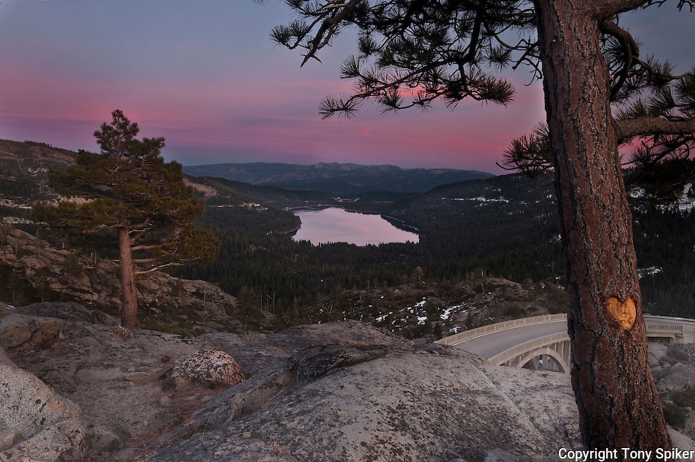 """Donner Lake Sunset 2"" - A photograph of the sun setting over Donner Lake with Rainbow Bridge in the foreground."