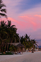 Clouds above White Sand Beach on Boracay Island reflect a vivid pink sunset in this tropical paradise.