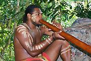 KURANDA, AUSTRALIA - NOVEMBER 07, 2007: Unidentified aborigine actor performs music with traditional didgeridoo musical instrument in the Tjapukai Culture Park in Kuranda, Queensland, Australia.