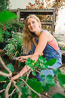 Portrait of a young woman working in a small plant nursery