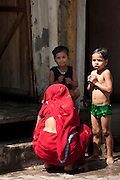 Indian children being bathed with water from a tap in the street by their mother in Agra, India