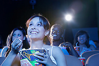 Young woman sitting in theatre eating popcorn watching movie