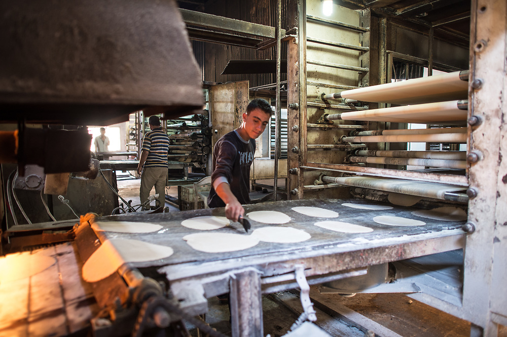 A men is making breads at the Kobanê Municipality Bakery. Kobanê (Ayn al-Arab), Syria, June 22, 2015