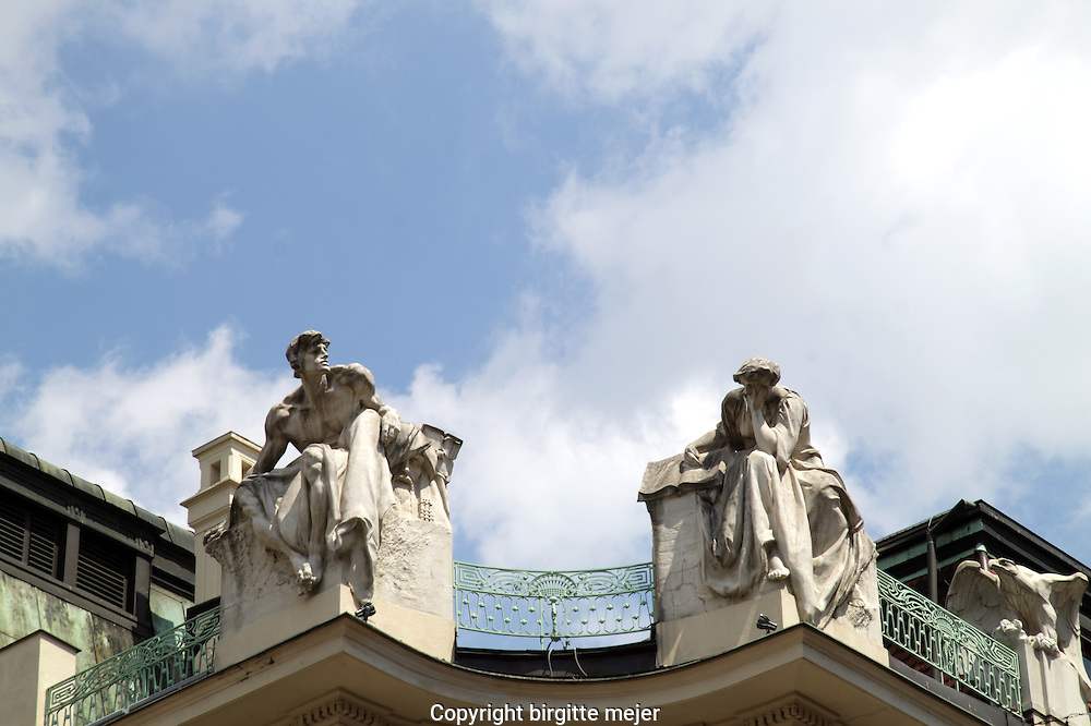 2 white sculptures on the top of a building in prague in the old town.<br />