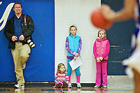 Bruce Twitchell cheeeses it up as he stands alongside three young girls Friday, Feb. 24, 2012 at the Coeur d'Alene High boys basketball game.