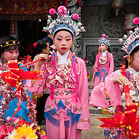 Children, dressed like Chinese opera performers and adorned with necklaces of money, wait for the procession of the Wenxing Mazu from the temple.  <br />