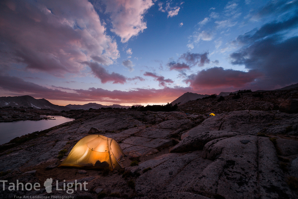 Lakeside camp and stormy sunset over Isoscolese peak, Mt. Winchell, Thunderbolt Peak, and North Palisade peak from a lake in the Dusy Basin in the High Sierra mountain range in California.