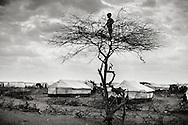 """Dollo Ado, Ethiopia.October2011<br /> In the refugeecamp """" Hilaweyn"""" also called """"Hells wind """" a small boy overlooks the massive camp which is now grown to more than 40.000 refugees... Refugees are still arriving in large numbers and due to that - relieforganisations have started to build a fifth camp in the area.<br /> Save the children  are working in all the camps, trying to improve the daily life for the many children in the camps.<br /> """" The drought in the horn of Africa is affecting more than 4.5 million people in Ethiopia. In addition, more than 140.000 refugees from Somalia have settled in camps in the border region between Somalia and Ethiopia. In the area around the border city Dollo Ado, four large refugee camps are already over crowded. A fifth camp is under construction due to the big influx still taking place. Many of the refugees are children, arriving severely malnutritioned. The mortality rate among small children has been brought down, but still children are dying on a daily basis...<br /> The four camps –Hilaweyn,Kobe, Malkadida and Bokomayo are now hosting more than 120.000 refugees and more are coming daily.... Somalia."""