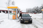 A man fills a car with petrol at an unmanned filling station in Sweden. The road is covered with snow.