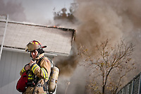 JEROME A. POLLOS/Press..Coeur d'Alene Fire Lt. Jeff Canfield talks on his radio Monday as smoke billows from a window of a house on Howard Street.