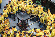 A temple group holds a palanquiin containing a god over a pile of firecrakcers during the Qingshan Wang festival.