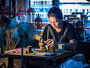"""02 NOVEMBER 2016 - BANGKOK, THAILAND:  GOB, who now runs the family spirit house workshop, works on the small figurines that """"live"""" in the spirit houses she makes. She makes the figurines in the living room of her home. There used to be 10 families making traditional spirit houses out of teak wood in Ban Fuen, a community near Wat Suttharam in the Khlong San district of Bangkok. The area has been gentrified and many of the spirit house makers have moved out, their traditional wooden Thai houses replaced by modern apartments. Now there is just one family making the elaborate spirit houses. The spirit houses are made by hand. It takes three days to make a small one and up to three weeks to make a large one. Prices start at about $90 (US) for a small one. The largest, most elaborate ones can cost over $1,000 (US). Almost every home and most commercial buildings in Thailand have a spirit house, which is a shrine to the protective spirit of a the land. Spirit houses are also common in Burma, Cambodia, and Laos.       PHOTO BY JACK KURTZ"""