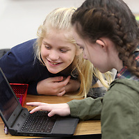 Elise Waters, 12, and Afton Gable, 12, work together to write code in a cheerleader routine code game. The girls were able to write the code for the cheers, dances and chants to happen for the cheerleader in the game during the Hour of Code at Milam Friday morning.
