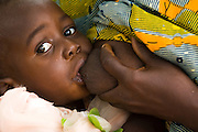 A mother breast feeds her child at the Adja-Ouere community health center in the village of Adja-Ouere, Benin and head out to remote villages to vaccinate children on Friday September 14, 2007.