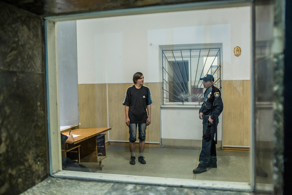 LVIV, UKRAINE - SEPTEMBER 16, 2015: A member of the new Lviv police watches over Vladimir, 26, left,  at a police station where he was taken for processing after he was found intoxicated and sleeping in the city's central square and then swore at police officers in Lviv, Ukraine. In an effort to reform the notoriously corrupt Ukrainian police force, an entirely new force has been established in several cities, including Kiev and Lviv, with a primary focus on patrolling the streets. CREDIT: Brendan Hoffman for The New York Times