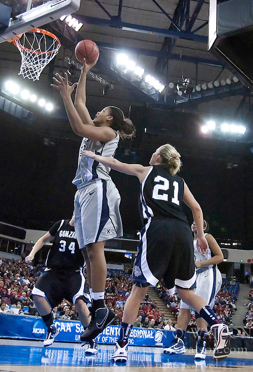 March 27, 2010; Sacramento, CA, USA; Xavier Musketeers center Brittney Moore (52) shoots past Gonzaga Bulldogs guard Courtney Vandersloot (21) during the second half in the semifinals of the Sacramental regional in the 2010 NCAA womens basketball tournament at ARCO Arena.  Xavier defeated Gonzaga 74-56.