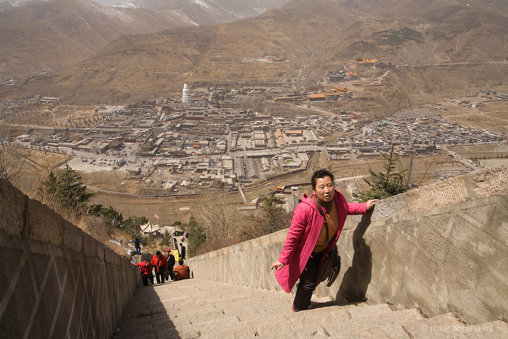 A pilgrim climbing up the steps to a temple in Wutai Shan, People's Republic of China
