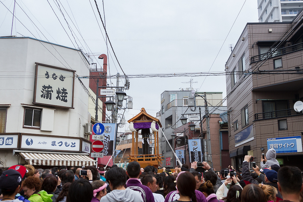 Festival supporters carry mikoshi or portable shrine with large phallus on them during the Kanamara Matsuri, (Festival of the Steel Phallus). Kawasaki Daishi, Kanagawa, Japan. Sunday April 3rd 2016. The famous Kawasaki Penis Festival started in 1977 as a small festival to celebrate an old legend about the defeat of a penis eating demon. Today the festival is a huge draw for Japanese and foreign tourists and raises money for HIV and AIDS research.