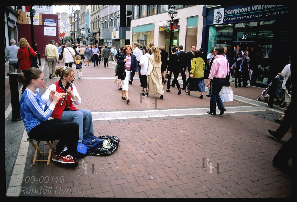 Pedestrians pass two girls playing flutes on Grafton Street, posh walking mall in downtown Dublin. Ireland