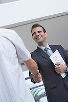 Male estate agent shaking hands with customer indoors