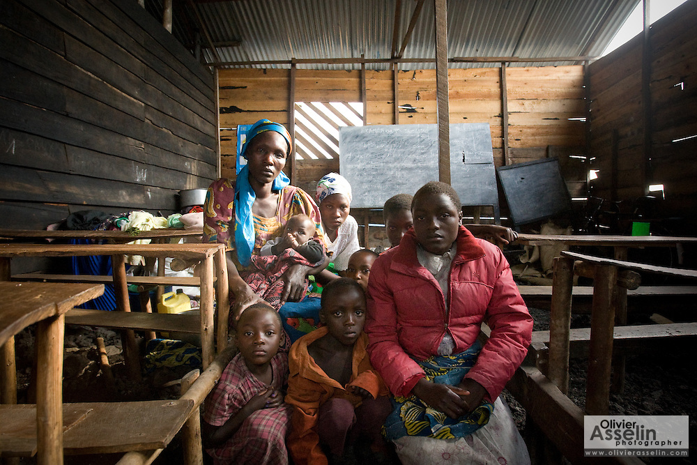 "Nyazaba Njabiya, 35, and her seven children in the classroom where they have lived for the past month at the Angalisho adventist primary school in Goma, Eastern DRC, on Sunday December 14, 2008. They came from Kibuma, 27km away, on the Rwandan border. Every morning, they vacate the classroom to allow children to attend school, and come back in the afternoon. ""We have no food, no water. Where we sleep, its very difficult,"" says Njabiya, adding that they can't go home because the rebels are still occupying their village. They walk 3km every day to fetch water from lake Kivu for their daily needs."