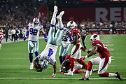 Dallas Cowboys quarterback Dak Prescott (4) gets upended by Arizona Cardinals cornerback Justin Bethel (28) and a teammate as he runs for a second quarter touchdown that ties the score at 7-7during the 2017 NFL week 3 regular season football game against the against the Arizona Cardinals, Monday, Sept. 25, 2017 in Glendale, Ariz. (©Paul Anthony Spinelli)
