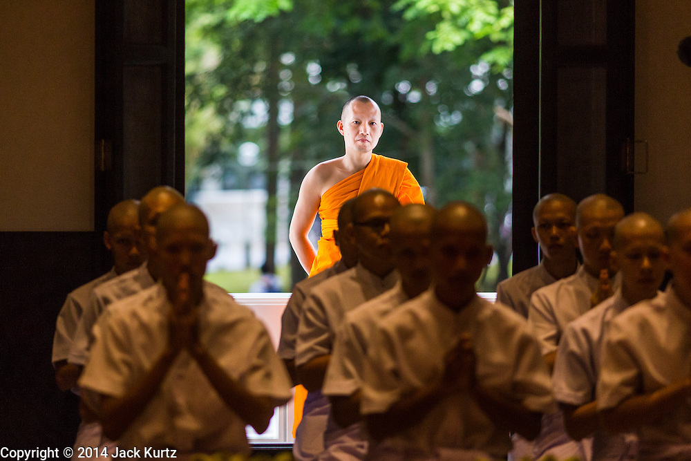 19 JULY 2014 - KHLONG LUANG, PATHUM THANI, THAILAND: A monk looks into the ordination hall during the ordination ceremony at Wat Phra Dhammakaya. Seventy-seven men from 18 countries were ordained as Buddhist monks and novices at Wat Phra Dhammakaya, a Buddhist temple  north of Bangkok, Saturday. It is the center of the Dhammakaya Movement, a Buddhist sect founded in the 1970s and led by Phra Dhammachayo (Phrathepyanmahamuni). It is the largest temple in Thailand. The Dhammakaya sect has an active outreach program that attracts visitors from around the world.    PHOTO BY JACK KURTZ
