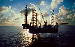 Stock photograph of oil and gas Jackup drilling rig at sunset in the Gulf of Mexico