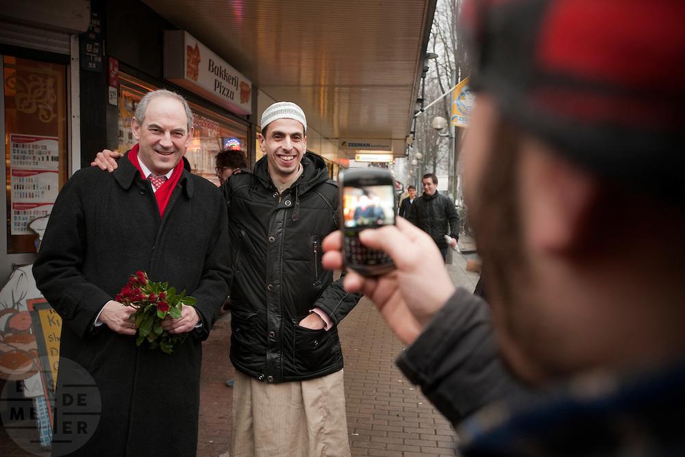 Job Cohen gaat op de foto met een potenti&euml;le allochtone kiezer in de Kanaalstraat in Utrecht. Cohen voert samen met Marleen Barth en Bert de Vries voor de PvdA campagne in Utrecht voor de Provinciale Statenverkiezingen.<br /> <br /> Job Cohen, leader of the Dutch Labour party PvdA is posing with a guy during a campaign at the Kanaalstraat in Utrecht.
