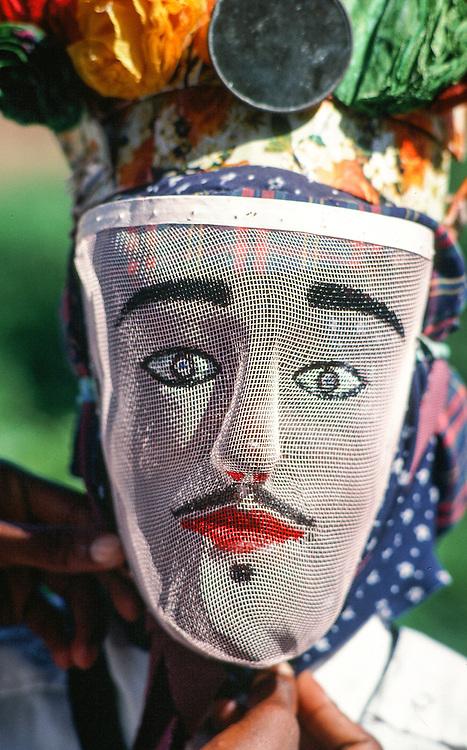Wanaragua dancer wearing garifuna mask of male painted on screen in Dangriga, Belize