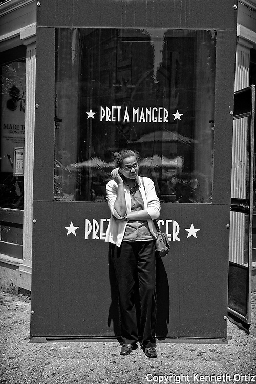 An African American woman waiting in front of Pret A Manger on the corner of 16th Street and Broadway, Downtown Manhattan, near Union Square.