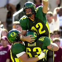 Univ. of Oregon's Jason Fife jumps into the arms of Dan Weaver after scoring the first touchdown on the first possesion of the 2002 season during the Ducks home opener against versus Mississippi State on Saturday Aug. 31, 2002. Photo by Timothy J. Gonzalez