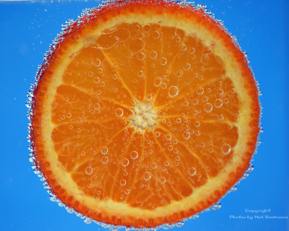 An orange slice submerged in sparkling water.
