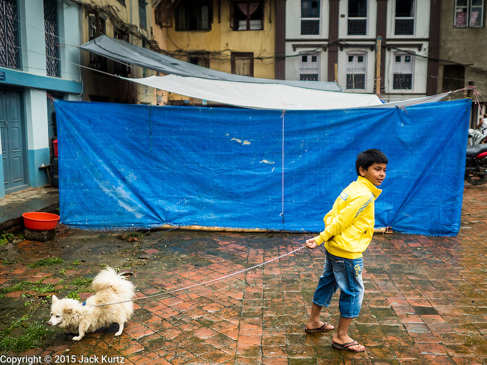 01 AUGUST 2015 - KATHMANDU, NEPAL: A boy in Kathmandu walks his dog in front of temporary housing for people displaced by the earthquake. The Nepal Earthquake on April 25, 2015, (also known as the Gorkha earthquake) killed more than 9,000 people and injured more than 23,000. It had a magnitude of 7.8. The epicenter was east of the district of Lamjung, and its hypocenter was at a depth of approximately 15km (9.3mi). It was the worst natural disaster to strike Nepal since the 1934 Nepal–Bihar earthquake. The earthquake triggered an avalanche on Mount Everest, killing at least 19. The earthquake also set off an avalanche in the Langtang valley, where 250 people were reported missing. Hundreds of thousands of people were made homeless with entire villages flattened across many districts of the country. Centuries-old buildings were destroyed at UNESCO World Heritage sites in the Kathmandu Valley, including some at the Kathmandu Durbar Square, the Patan Durbar Squar, the Bhaktapur Durbar Square, the Changu Narayan Temple and the Swayambhunath Stupa. Geophysicists and other experts had warned for decades that Nepal was vulnerable to a deadly earthquake, particularly because of its geology, urbanization, and architecture.          PHOTO BY JACK KURTZ