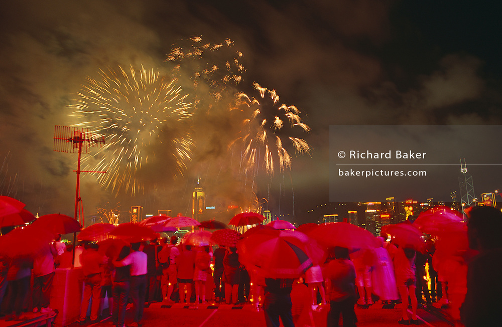"In heavy monsoonal rain, crowds gather at the stroke of midnight beneath umbrellas to witness the transfer of sovereignty of Hong Kong from the United Kingdom to the Peoples Republic of China (PRC), often referred to as ""The Handover"" on June 30, 1997. Midnight signified the end of British rule, and the transfer of legal and financial authority back to China. From the on the roof of Ocean Terminal shopping mall, the skyline is filled with fireworks but the glowing red comes from giant advertising lettering behind the viewer on the top floor of the building which protrudes out into Hong Kong harbour from the Kowloon side of the territory.  Hong Kong was once known as 'fragrant harbour' (or Heung Keung) because of the smell of transported sandal wood."