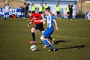 Brighton's Deanna Cooper is shadowed by Hassocks' skipper Liz King during the FA Women's Sussex Challenge Cup semi-final match between Brighton Ladies and Hassocks Ladies FC at Culver Road, Lancing, United Kingdom on 15 February 2015. Photo by Geoff Penn.