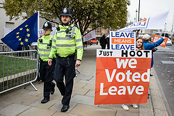 © Licensed to London News Pictures. 10/01/2019. London, UK. Police officers walk past pro-Brexit protesters gathered opposite the Palace of Westminster. There is an increased police presence around Parliament after Conservative MP Anna Soubry was targeted by far-right activists. Photo credit: Rob Pinney/LNP