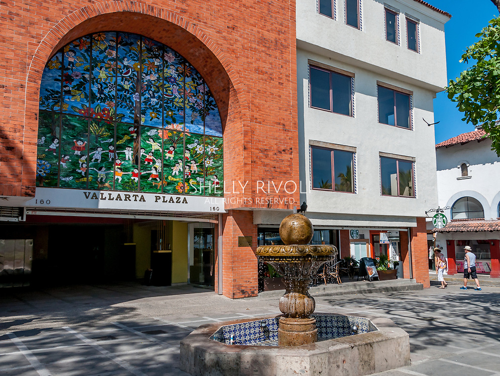 Stained glass by Manuel Lepe at Vallarta Plaza, bird on fountain, and toursits walking through Old Town square, Romantic Zone, Puerto Vallarta.