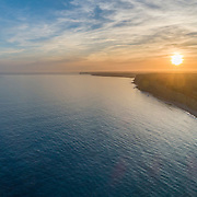 Aerial sunset seascape, of Praia Porto de Mos (Beach and seaside cliff formations along coastline of Lagos city), famous destination in Algarve. South Portugal.