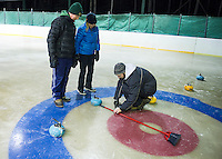 Jim and Judy McShane look on as Herb Greene of Gilford Parks and Rec takes the official measurement on the stones during the weekly curling tournament at the Gilford Ice Rink on Thursday evening.  (Karen Bobotas/for the Laconia Daily Sun)