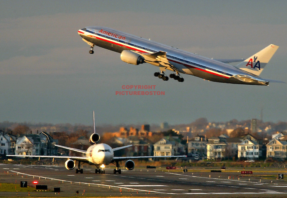 "Various airliners flying in and around Boston's Logan International Airport. Very long lens. NO trickery or photoshop. All photos are ""real time"" with no trickery or multiple exposure. Here, a Boeing 777 flies over an MD-11"
