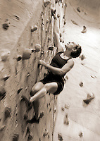 Woman practicing rock climbing in indoor facility (B&W sepia) low angle view (focus on face, digital enhancement)