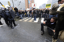 A dairy farmer squirts police with milk as farmers from a cross Europe gathered in Brussels in protest of European Union agricultural policy, as a meeting of EU agriculture ministers convened, on Monday, Oct. 5, 2009. (Photo © Jock Fistick)