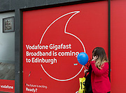 A Scots woman holding a blue balloon, talks on her phone outside a Vodafone shop advertising Gigafast Broadband, on Prince's Street in Edinburgh, on 25th June 2019, in Edinburgh, Scotland.
