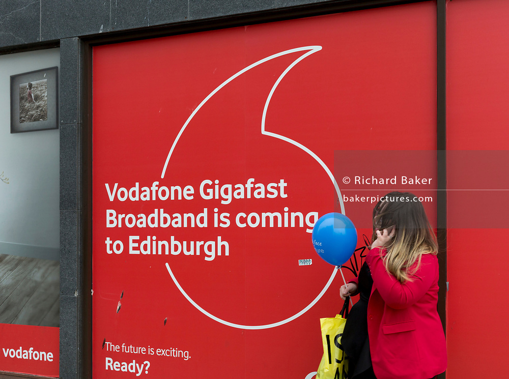 A Scots woman holding a blue balloon, talks on her phone outside a Vodafone shop advertising Gigafast Broadband, on Prince's Street in Edinburgh, on 25th June 2019, in Edinburgh, Scotland.