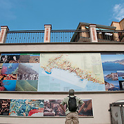 A male tourist wearing a black back pack studies a map in Manarola (Punta Buonfiglio) looking for the different villages in the Cinque Terre region of Western Italy.